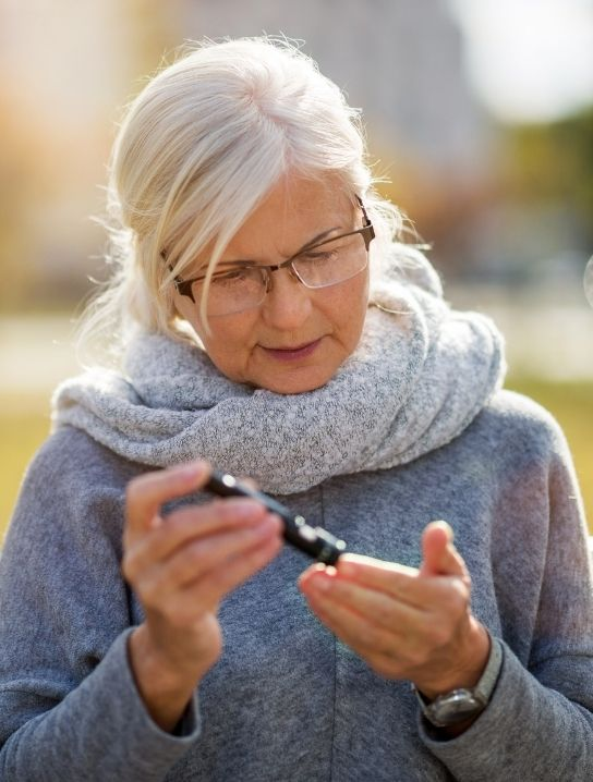 Senior-checking-her-blood-sugar-using-a-tester-comfort-home-health-agency
